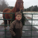 With one of the horses (belongs to his special neighbor-friend)